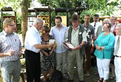 Achim Tüttenberg MdL und stellv. Bürgermeister Troisdorfs M. Catrin überreichen Werner Funken die UN-Dekade-Auszeichnung